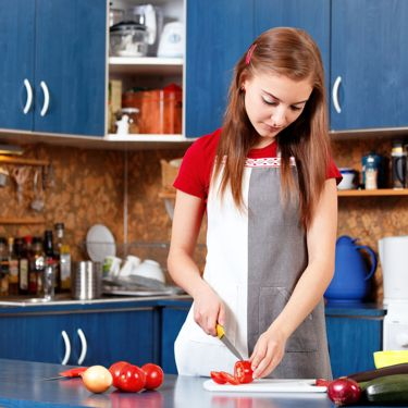 young girl cutting tomato in the kitchen
